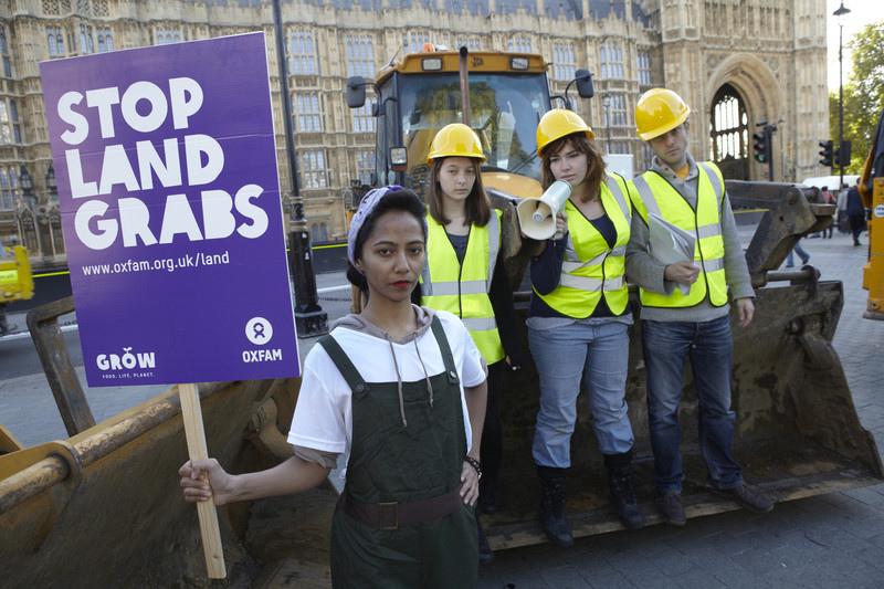 Oxfam protestors demonstrate against land grabbing in Westminster, UK. 2012 [Oxfam International/Flickr]